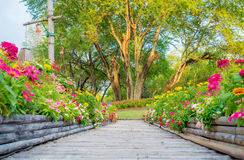 Wooden bamboo path way with beautiful flowers Stock Photos