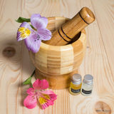 Wooden bamboo pounder with bottles of oils and. Wooden bamboo pounder with bottles of oils Stock Image