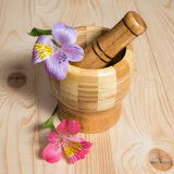 Wooden bamboo pounder. With flowers on wooden background Royalty Free Stock Image