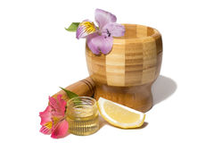 Wooden bamboo pounder with flowers isolated. Wooden bamboo pounder with flowers and honey Royalty Free Stock Images