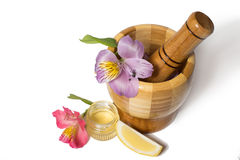 Wooden bamboo pounder with flowers isolated. Wooden bamboo pounder with flowers and honey Royalty Free Stock Photos
