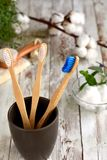 Wooden bamboo toothbrushes in dark brown glass royalty free stock photo