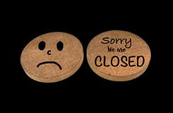 "Wooden banner with text ""Sorry, We are Closed"" and sad symbol isolated on black background with clipping path. Wooden banner with text ""Sorry, We stock photo"