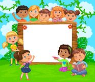 Wooden banner with white blank paper and cute kids on green meadow royalty free stock image