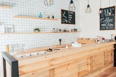 Wooden bar counter of modern cafe decorated with white tiles royalty free stock photos