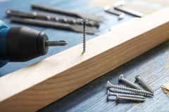 Wooden bar, screw nails and drill on table in carpenter`s workshop. Closeup Stock Photography