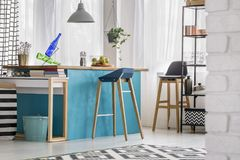 Modern blue dining room. Wooden bar stool at blue table under grey lamp in modern dining room with bucket and shelves Stock Image