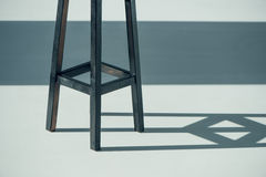 Wooden bar stool. Cropped shot of wooden bar stool and shadow on grey Royalty Free Stock Images