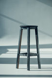Wooden bar stool. View of wooden bar stool with shadows on grey Royalty Free Stock Images