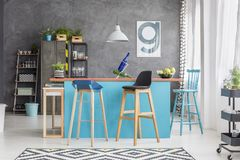 Wooden bar stools at table. Wooden bar stools at dining table under lamp in interior with locker and poster on grey wall Royalty Free Stock Photos