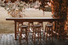 Bar table outside in autumn. Wooden bar table and chairs outside in autumn garden Stock Photography