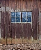 Wooden Barn with Double Windows. Old wooden barn with double windows. Reflection of trees in window panes. Shot vertically stock image