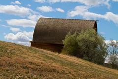 Wooden Barn on a Hill with Cumulus Clouds Royalty Free Stock Photos
