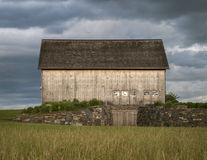 Wooden Barn on Hilltop Before A Storm. Old wooden barn on the side of a hill with a storm overhead Stock Photography