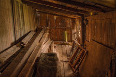 Wooden barn interior. Dark wooden barn interior with pile of wooden boards and frames Royalty Free Stock Photography