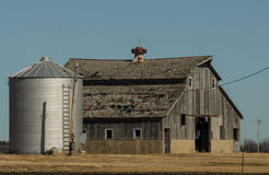 Wooden barn and silo. The old vintage wooden barn and silo in the open Midwest field Royalty Free Stock Images