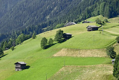 Wooden barns for hay at the slope of a mountain Stock Image