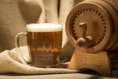 Wooden barrel with beer mug on canvas background Royalty Free Stock Images