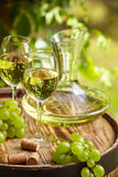 Wooden barrel with bottle and glass of white wine. Stock Photos