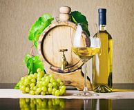 Wooden barrel with grape twig and bottle of white wine stock photos