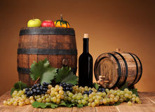 Wooden barrel, grapes and wine in the bottle Stock Images