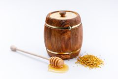 A wooden barrel of honey and a wooden spoon with a drop of tasty liquid and a scattering of pollen on a white background. Close-up royalty free stock photo