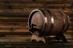 Wooden barrel with iron rings on a brown wooden background Stock Images