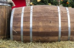 Wooden barrel with metal hoops. Oak barrel on straw stock photos