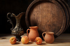 Wooden barrel, peach and ceramic dishes Stock Photos