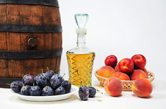 Wooden barrel, plum, peach and brandy Stock Photo