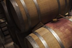 Wooden barrels with red wine in dark winery. Close up photo with selective focus Royalty Free Stock Image
