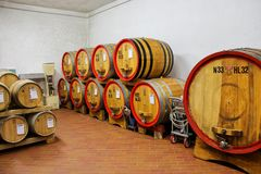 Wooden barrels in a wine cellar in Montalcino, Val d`Orcia, Tusc. Any, Italy. Montalcino is famous for its Brunello di Montalcino wine stock images