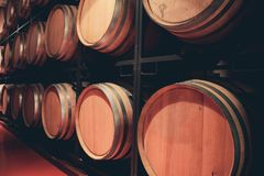 Wooden barrels with wine in dark cellar. royalty free stock image