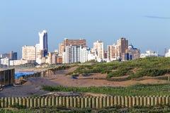 Wooden Barrier and Dune Vegetation Against  City Skyline Stock Images