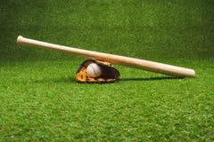 Wooden baseball bat with ball and glove on green grass. Close-up view of wooden baseball bat with ball and glove on green grass Royalty Free Stock Image