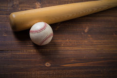 A wooden baseball bat and ball on a wooden background Stock Photography