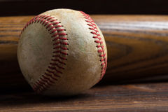 A wooden baseball bat and ball on a wooden background royalty free stock photo