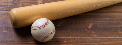A wooden baseball bat and ball on a wooden background royalty free stock image