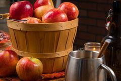 Basket of apples with cup of cider blurred in foreground Royalty Free Stock Image