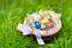 Wooden basket with colorful Easter eggs and flowers Royalty Free Stock Photo
