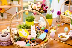 Wooden basket with easter composition, sweets, choco, gingerbrea. D standing on brown table decorated with easter colored eggs, paints, tassels and flowers Stock Images