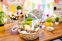 Wooden basket with easter composition, sweets, choco, gingerbrea. D standing on table decorated with easter colored eggs and flowers Royalty Free Stock Image