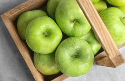 Wooden basket with fresh green apples. On table stock photography