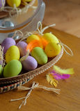 Wooden basket full of colorful eggs and bird Royalty Free Stock Photos