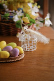 Wooden basket full of colorful eggs and bird Royalty Free Stock Images