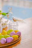 Wooden basket full of colorful eggs and bird Stock Photo