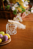 Wooden basket full of colorful eggs and bird Stock Images