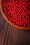 A wooden basket full of juicy and red currant on a dark brown wooden background. Healthy, fresh and berries in the brown crate. Stock Photo