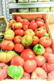 A wooden basket full of tomatoes fresh. A wooden basket full of Vegetables in an organic fruits and vegetables store in Paris Stock Photography