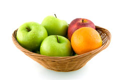 Wooden basket with mixed fruit. Isolated on white background royalty free stock images